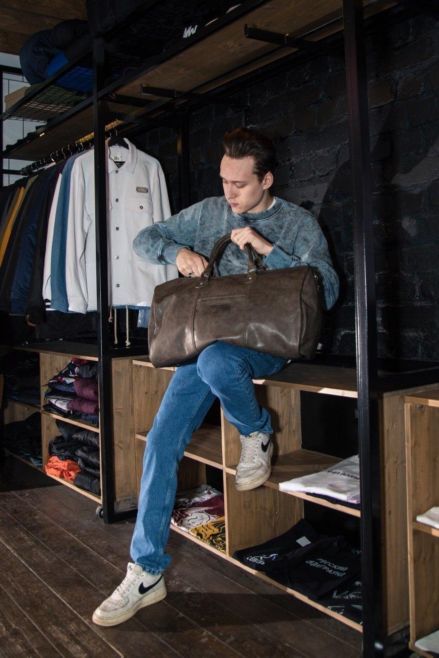 Молодой человек с дорожной сумкой - фотография